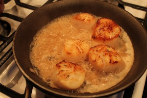 Scallops searing and reducing in the sauce.